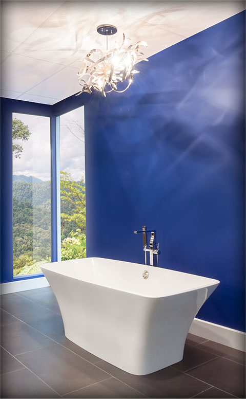 Photo of a bathtub on a grey tiled floor with blue walls behind.